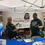 Two cancer survivors volunteer at Be The Match booth at University of Hawaii football game